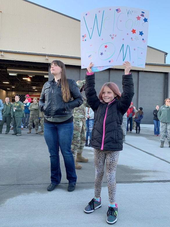 """Liela Adamson, age 10, eagerly holds up her handmade """"welcome home"""" sign while her mom, Kyleah Adamson, tries to get a glimpse of her boyfriend, Tech. Sgt. Logan Everton, who returned to Hill Air Force Base early Friday following a six-month deployment to Al Dhafra Air Base, United Arab Emirates"""
