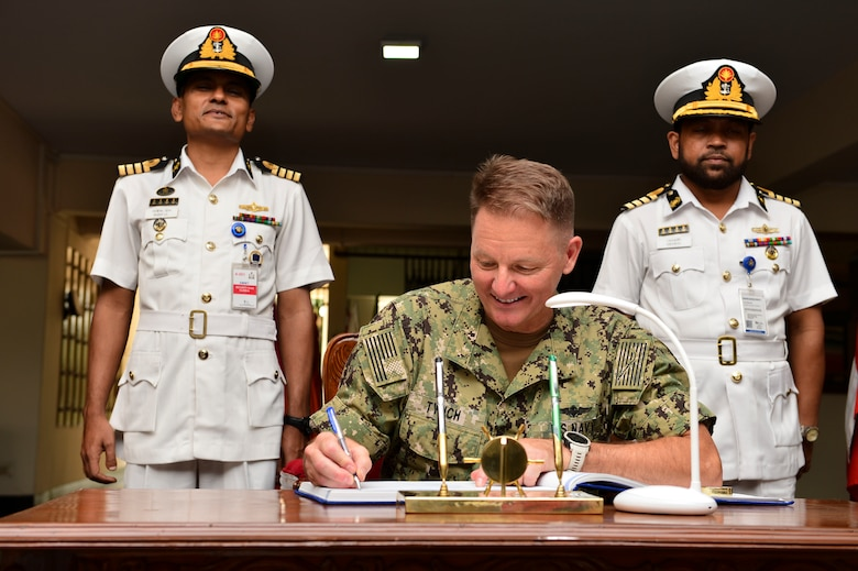 Chattogram, Bangladesh. (Nov. 4, 2019) Rear Adm. Joey Tynch, commander, Logistics Group Western Pacific, signs the guest book during the opening ceremony for Cooperation Afloat Readiness and Training (CARAT) Bangladesh 2019. This year marks the 25th iteration of CARAT, a multinational exercise designed to enhance U.S. and partner navies' abilities to operate together in response to traditional and non-traditional maritime security challenges in the Indo-Pacific region.
