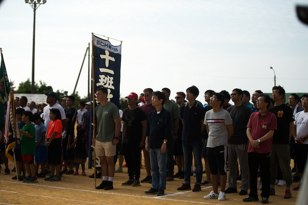 U.S. Marines with 4th Marine Regiment, 3rd Marine Division, and Okinawa residents stand for the playing of the Japanese National Anthem during the opening ceremony for the 46th Annual Henoko District Citizen's Track and Field Meet Sports Day in Henoko, Okinawa, Japan, Nov. 3, 2019. Personnel from Camp Schwab have been included in the track and field meet since 1973 and will carry on the tradition of good will and togetherness with the people of Henoko. (U.S. Marine Corps photo by Cpl. Josue Marquez)