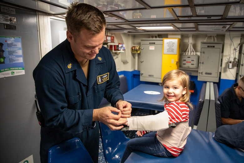 191101-N-AD347-0101 SASEBO, Japan (November 01, 2019) Chief Hospital Corpsman, Kenneth Van Tassel, bandges up his daughter for fun to show her what he does at work aboard Avenger-class mine countermeasures ship USS Pioneer (MCM 9). Pioneer, part of Mine Countermeasures Squadron 7, is operating in the 7th Fleet area of operations to enhance interoperability with partners and serve as a ready-response platform for contingency operations.