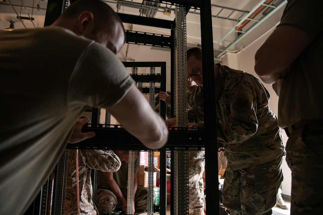 Master Sgt. Jonathan Reis, 205th Engineering and Installation Squadron non-commissioned officer in charge for electronics, works with a rack that will hold radios along with other 205th EIS team members in a storage room at Andersen Air Force Base in Guam on Sept. 15, 2019. The 205th EIS had seven Airmen working to install ten CM-300/350 radios in the 36th Operations Support Squadron air traffic control tower in Guam as part of the U.S. Air Force Air Traffic Control and Landing Systems Radio Replacement Program. (U.S. Air National Guard photo by Staff Sgt. Brigette Waltermire)