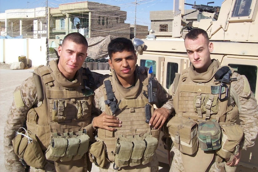 Three Marines in combat gear pose for a photo against a dusty, remote-looking landscape.