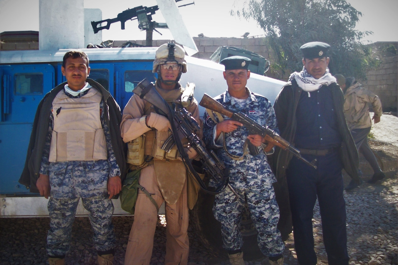 Four men dressed in different uniforms pose for a photo with an armored vehicle behind them. The two men in the middle are holding weapons.