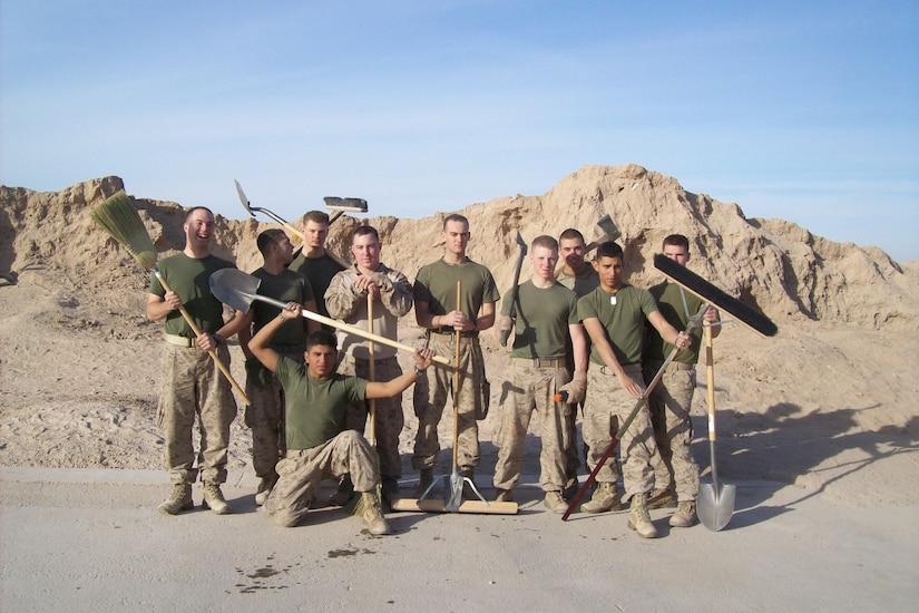 Ten Marines holding cleaning and digging tools pose for a photograph with large mounds of sand in the background.