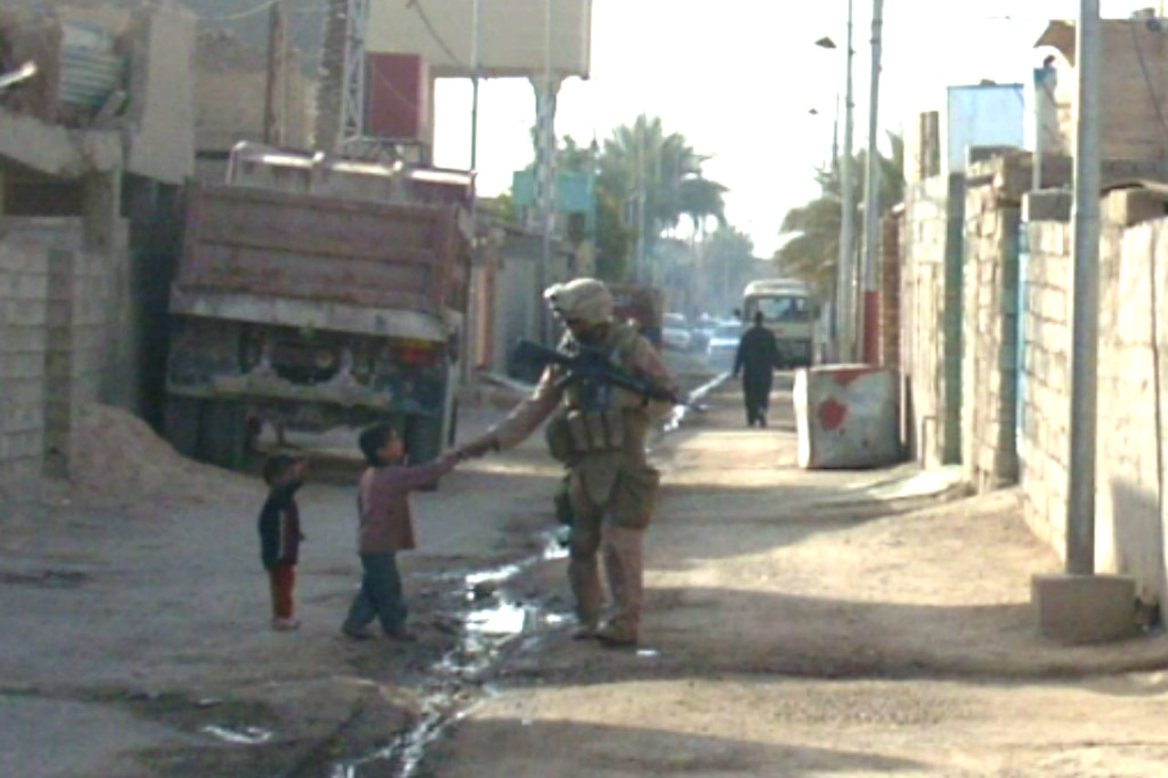 Walking down a narrow, dirt street lined with walls made of concrete blocks, a Marine in combat gear stops to shake the hand of a  small child while another child looks on.from a distance.