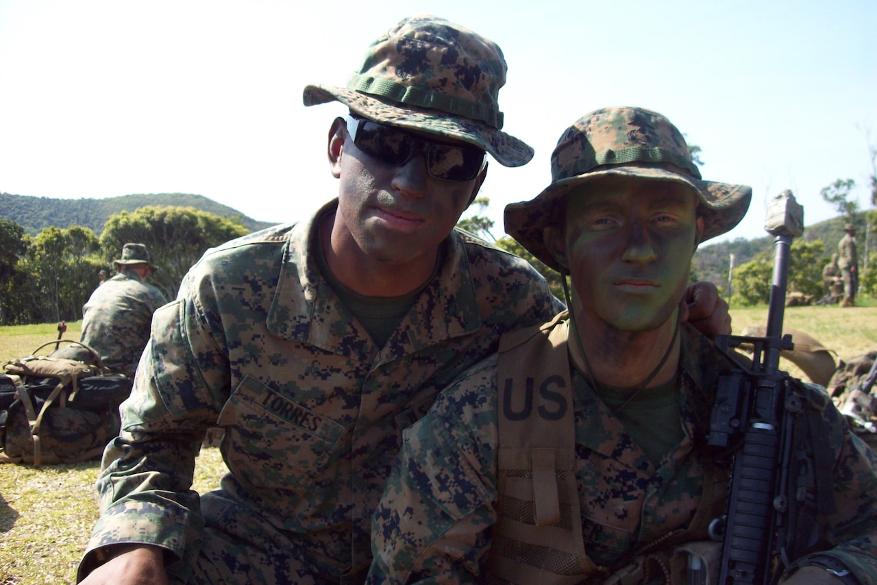 Two Marines,  wearing camouflage uniforms and camouflage face paint, pose for a photo in a field with trees in the background.