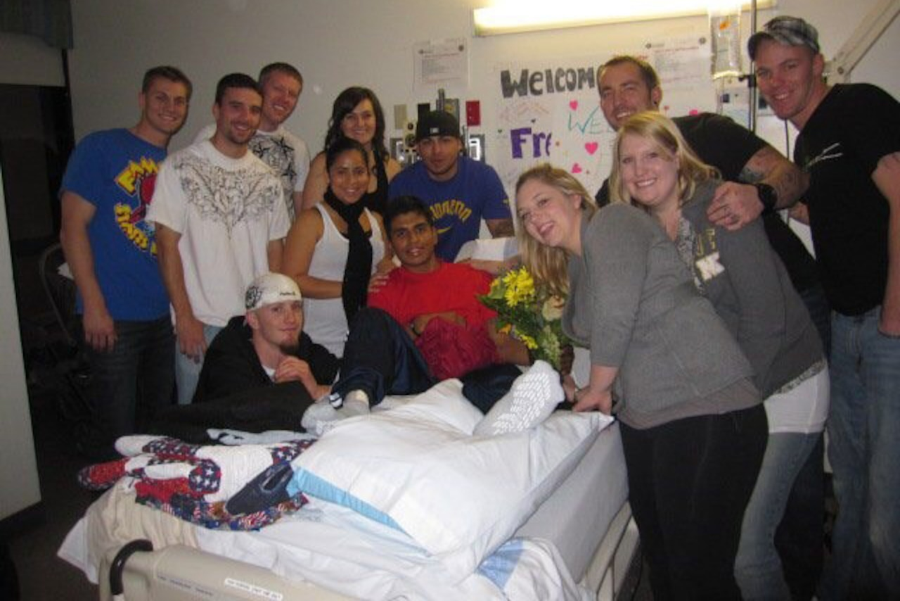 Eleven people surround a young man lying in a hospital bed with his leg bandaged and propped up on a pillow.