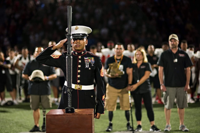 A Marine in dress uniform salutes a weapon pointing downward atop a wooden box on a football field. Four people, including a woman and two men with prosthetic legs look on from behind; football players stand in the background.