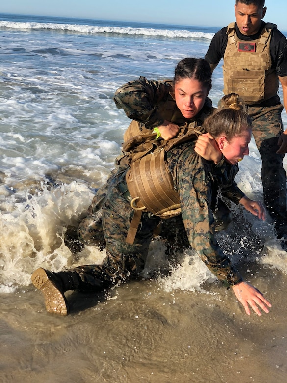 A male Marine watches two female Marines who are practicing martial arts in the ocean near a beach.