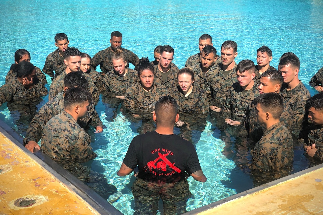 A Marine instructor with his back to the camera instructs about two dozen Marines in fatigues who are huddled in front of him in a swimming pool.