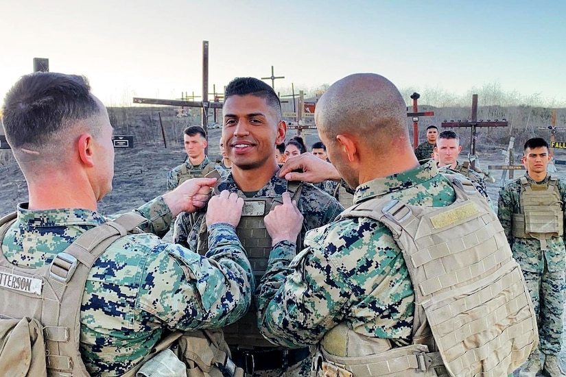 Two Marines pin new rank insignia on the lapels of another Marine, as at least eight Marines look on.