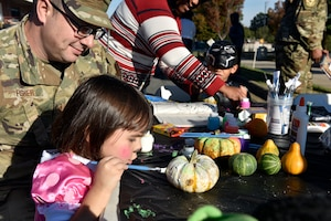 A young girl paints a pumpkin during a Fall Festival put together by the Junior Enlisted Council (JEC) at the North Carolina Air National Guard (NCANG) Base, Charlotte Douglas International Airport, Nov. 2, 2019. The Fall Festival is a first-time event for the JEC and NCANG that is hoped to be held for years to come.