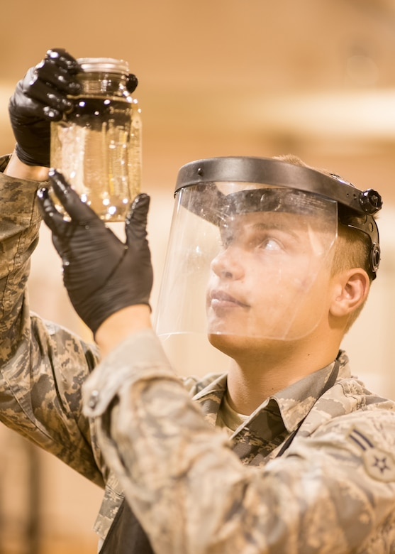 Airman 1st Class Austin Stepp, 436th Logistics Readiness Squadron fuels distribution operator, inspects a jet fuel sample for sediment and discoloration, Oct. 29, 2019, at Dover Air Force Base, Del. Fuel is inspected daily to ensure all aircraft get the cleanest fuel possible. (U.S. Air Force photo by Mauricio Campino)