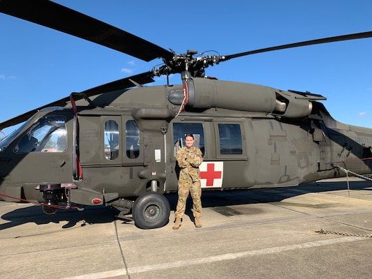 1LT Hollianne M. Peal stands in front of a UH-60 Blackhawk helicopter on a landing pad.