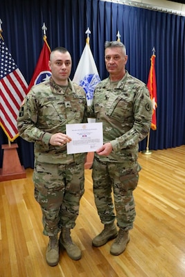 Maj. Gen. Jeff Holmes, Tennessee's adjutant general, presents Sgt. Ryan Grillo, a Soldier with the 1176th Transportation Company, the adjutant general's Ribbon for Valor on Nov. 2. Grillo and another citizen rescued two women and a small child from flood waters in Athens Sept. 26, 2018.