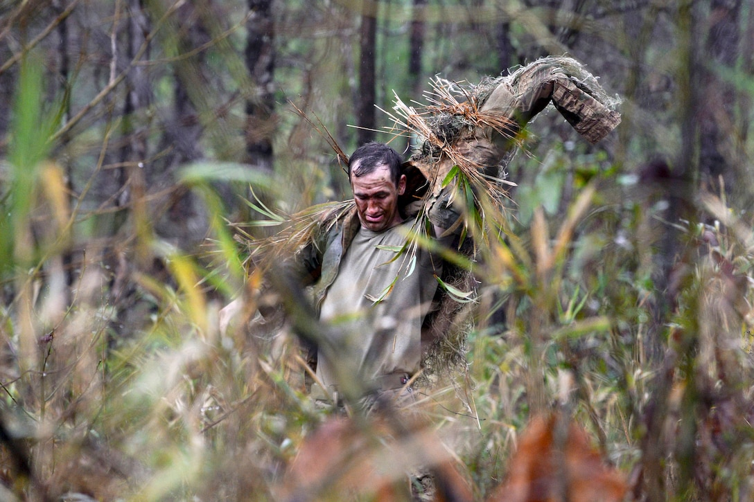 A soldier puts on his ghillie suit after adding natural vegetation.