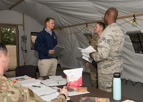 Second Lt. Shawn Edgecomb and Senior Airman Brandon Williams, both contracting administrators with the 509th Contracting Squadron, report to the command tent during a mock deployment exercise, Oct. 9, 2019, at Whiteman Air Force Base, Missouri. Squadron leadership reviewed and evaluated each team's work throughout the exercise, which challenged them to support the setup of a notional deployed base in Mogadishu, Somalia. (U.S. Air Force photo by Airman 1st Class Parker J. McCauley)