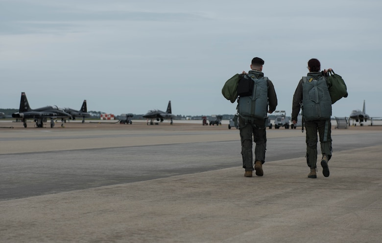 Vivienne Machi, Defense Daily reporter, and 1st Lt. Josh Burdge, 71st Fighter Training Squadron pilot, walk toward T-38A Talons during a familiarization flight at Joint Base Langley-Eustis, Virginia, Oct. 31, 2019. Machi experienced firsthand how 1st FW pilots train at JBLE. (U.S. Air Force photo by Airman 1st Class Sarah Dowe)