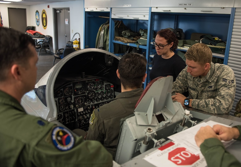 Vivienne Machi, Defense Daily reporter, and Airmen, learn about emergency procedures during SERE training at JBLE, Virginia, Oct. 31, 2019. The training is required before taking part in a familiarization flight. (U.S. Air Force photo by Airman 1st Class Sarah Dowe)
