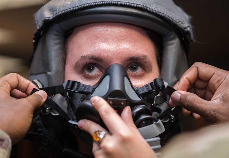 Vivienne Machi, Defense Daily reporter, gets fitted for a helmet and air mask before a familiarization flight at Joint Base Langley-Eustis, Virginia, Oct. 31, 2019. Machi flew in a T-38A Talon during an adversary air training with the F-22 Raptor. (U.S. Air Force photo by Airman 1st Class Sarah Dowe)