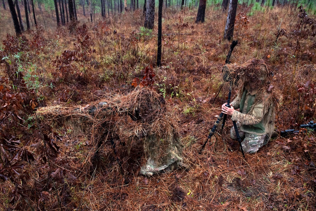 Army sniper school graduates setup a camouflage demonstration.