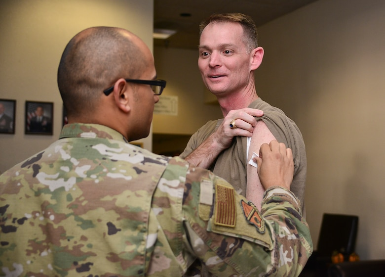 From left, U.S. Air Force Tech. Sgt. Mircho Plaza, 377th Medical Group Allergy and Immunology technician, gives U.S. Air Force Col. David S. Miller, 377th Air Base Wing commander, his influenza vaccination at Kirtland Air Force Base, N.M., Nov. 1, 2019. The flu shot is now available to active duty service members, who are required annually to receive the vaccine. (U.S. Air Force photo by Staff Sgt. Kimberly Nagle)