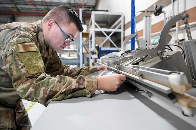 Senior Airman Alec Couture, munitions inspector with the 649th Munitions Squadron, heat seals a barrier bag, which holds assets for repackaging, with newly acquired equipment. The squadron recently purchased new electrostatic discharge workstations with Air Force Material Command squadron innovation funds, which has helped the squadron inspect incoming and outgoing munitions faster and safer.
