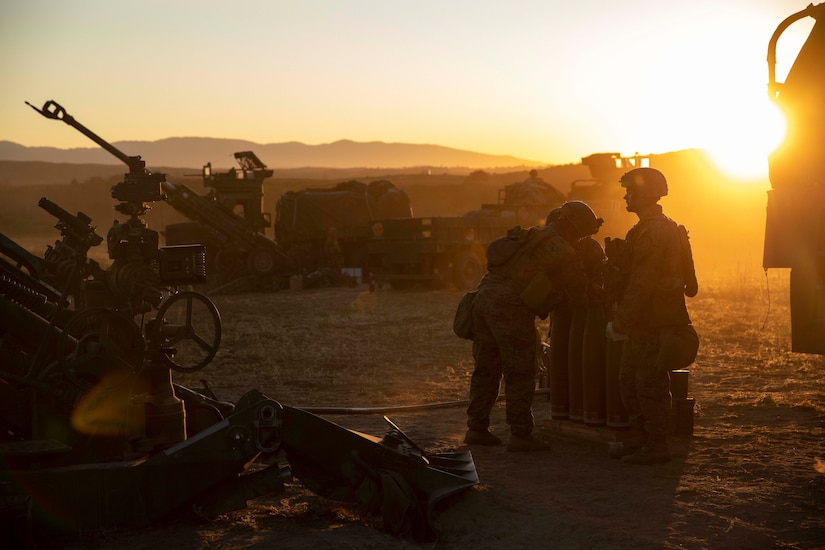 Artillery and Marines gather at dusk in the field