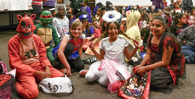 A group of Kirtland Elementary School students pose for a photo during a trick-or-treat event on Kirtland Air Force Base, N.M., Oct. 31, 2019. Each year, SMC invites the school to their Haunted Halloween event in which the entire building is filled with spooky decorations and hundreds of pounds of candy are passed out to costumed visitors.