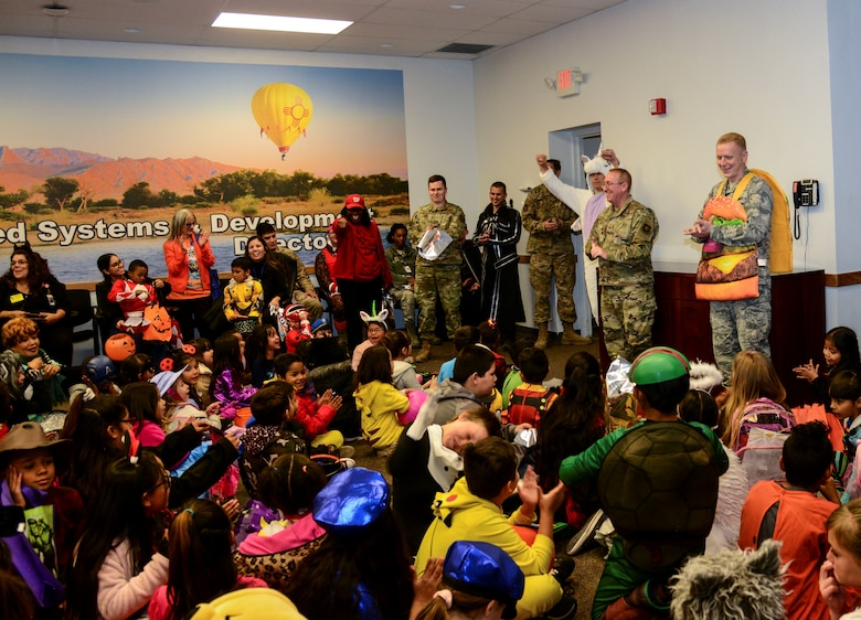 Kirtland Elementary School students and teachers listen to a briefing from members of the Space and Missiles Systems Center (SMC) on Kirtland Air Force Base, N.M., Oct. 31, 2019. Each year, SMC invites the school to their Haunted Halloween event in which the entire building is filled with spooky decorations and hundreds of pounds of candy are passed out to costumed visitors.