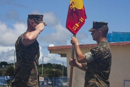 Gunnery Sgt. Jared McManus, company first sergeant for Maneuver Company, salutes 1st Lt. Sean Gunn, company commander of Maneuver Company, during the company activation ceremony at Camp Hansen, Okinawa, Japan, Aug. 30, 2019.