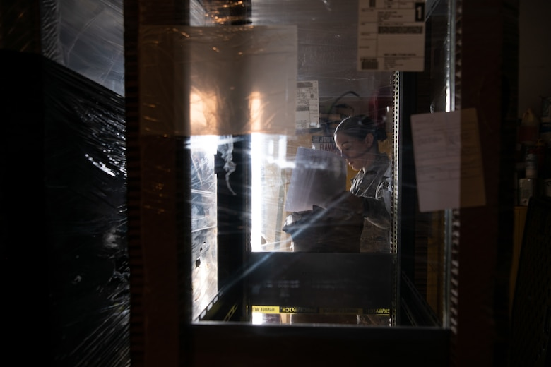 Tech. Sgt. Allison Dzon, cable antenna systems Airman for the 205th Engineering and Installation Squadron and team chief for the installation project, goes through an inventory list as she checks off the plastic-wrapped racks in a storeroom at Andersen Air Force Base in Guam on Sept. 9, 2019. The 205th EIS out of Oklahoma City had seven Airmen working to install ten CM-300/350 radios on racks in the 36th Operations Support Squadron air traffic control tower in Guam as part of the U.S. Air Force Air Traffic Control and Landing Systems Radio Replacement Program. (U.S. Air National Guard photo by Staff Sgt. Brigette Waltermire)