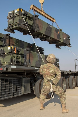 A soldier from Alpha Battery, 4th Battalion, 5th Air Defense Artillery, 69th Air Defense Artillery Brigade works with his team removes missiles from a trailer in preparation to reload their Patriot Launching Station.