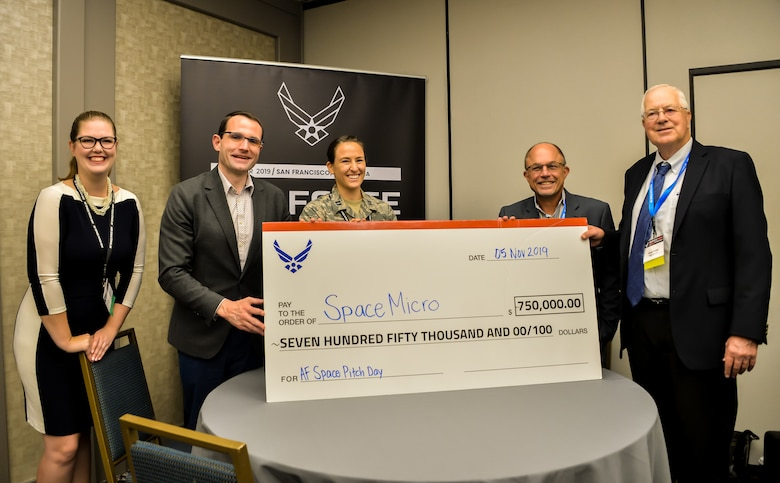 Dr. William Roper, Assistant Secretary of the Air Force for Acquisition, presents the first giant check of $750,000 at Air Force Space Pitch Day, Nov. 5, 2019, San Francisco, Calif. Air Force Space Pitch Day is a two-day event hosted by the Air Force to demonstrate the Air Force's willingness and ability to work with non-traditional startups. (U.S. Air Force photo by Van De Ha)