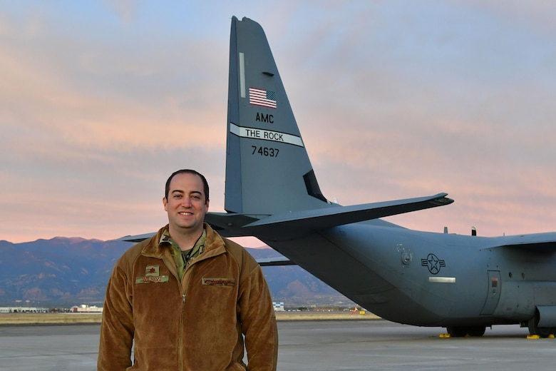 The assistant director of operations poses for a photo in front of a C-130 in Colorado.