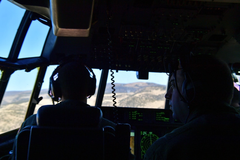 An instructor observes and records how a student pilot responds to complex training situations over Colorado.