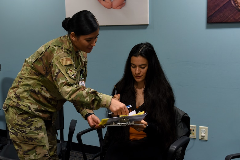 Senior Airman Jamie Eriksson, 48th Surgical Operations Squadron Obstetrics/Gynecologist medical technician, assists a patient during the Village Friends Group Obstetrics Care meeting at Royal Air Force Lakenheath, England, Oct. 25, 2019. The program provides prenatal care in a group setting of 8-12 women with similar due dates. (U.S. Air Force photo by Airman 1st Class Rhonda Smith)