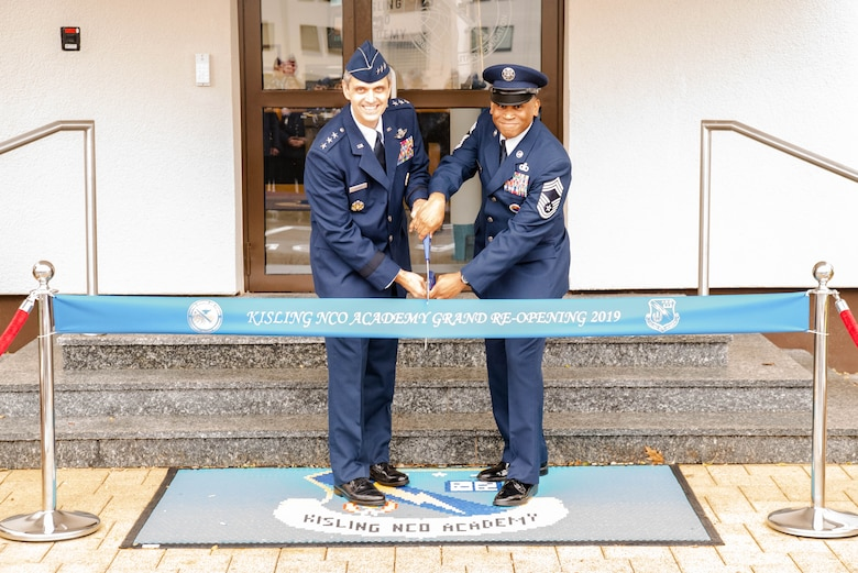 U.S. Air Force Lt. Gen. Steven L. Basham, United States Air Forces in Europe – Air Forces Africa deputy commander, and Chief Master Sgt. Terrance Smiley, Kisling Noncommissioned Officer Academy commandant, prepare to cut a ribbon for the NCOA's reopening on Kapaun Air Station, Germany, Nov. 1, 2019. The NCOA underwent extensive renovations to update the building, restrooms, classrooms, and offices, allowing students and instructors to better focus on professional military education. (Courtesy Photo)