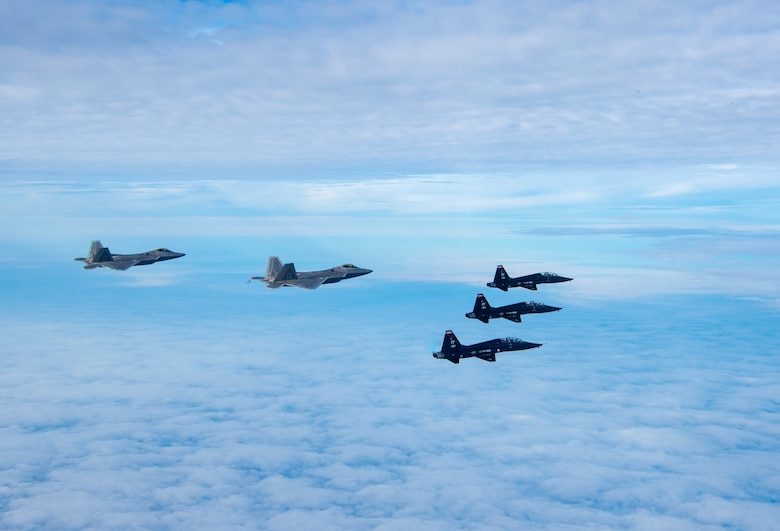 U.S. Air Force F-22 Raptors and U.S. Air Force T-38 Talons from the 1st Fighter Wing fly in formation of the Atlantic Ocean during training off the coast of Virginia, Oct. 30, 2019. The 1st Fighter Wing is home to the 94th Fighter Squadron, 27th Fighter Squadron and the 71st Fighter Training Squadron at Joint Base Langley-Eustis, Va. (U.S. Air Force Photo by Tech Sgt. Carlin Leslie)(Released)