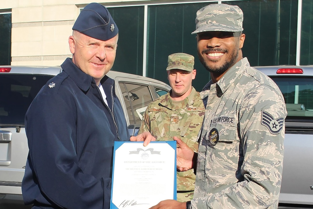 655th Intelligence, Surveillance, and Reconnaissance Wing, 16th Intelligence Squadron Commander Lt. Col. Jeffrey Derr presents the Air Force Achievement Medal to Staff Sgt. Caldwell (first name withheld) November 2, 2019.  Caldwell earned the medal for heroic actions on October 6, when he saved a young girl's life by preventing her from jumping off an interstate on-ramp.  First responders claimed the 60-foot drop would have been fatal. (Courtesy photo)