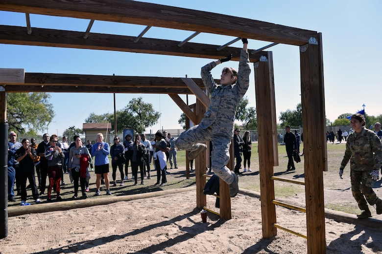 Staff Sgt. Alexis J. Kempel, 433rd Force Support Squadron force management technician, crosses the monkey bars during the 433rd Airlift Wing Resilience Tactical Pause at the Air Force Basic Military Training's Basic Expeditionary Airman Skills Training site at the Medina Annex, Joint Base San Antonio-Lackland, Texas Nov. 3, 2019.