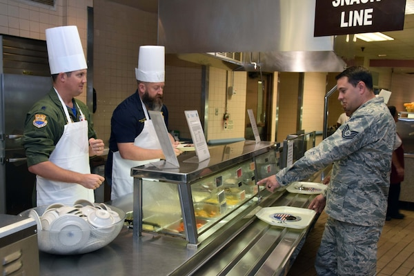 Lt. Col. William A. Dabney, 433rd Contingency Response Flight commander, and Honorary Commander Andrew Camplen, post commander, Pvt. Bruno Phillip Veterans of Foreign Wars, Post 688, serve food to 433rd Airlift Wing and 960th Cyberspace Wing members at the Live Oak Dining Facility at Joint Base San Antonio-Lackland, Texas Nov. 2, 2019.