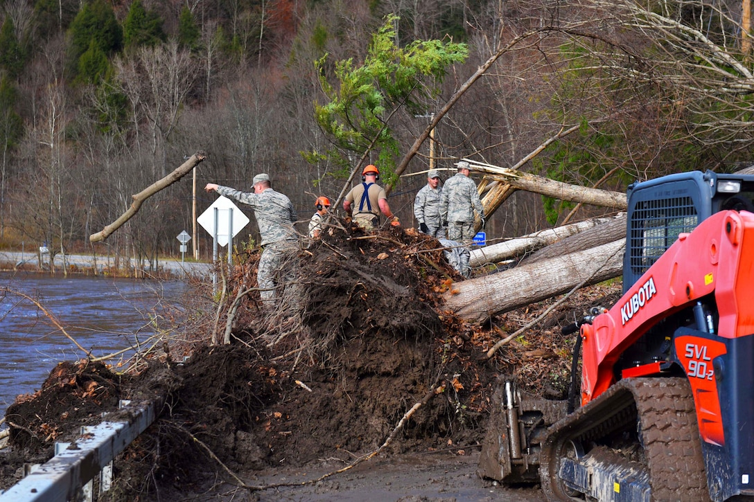 National Guard airmen clear debris from blocked road.