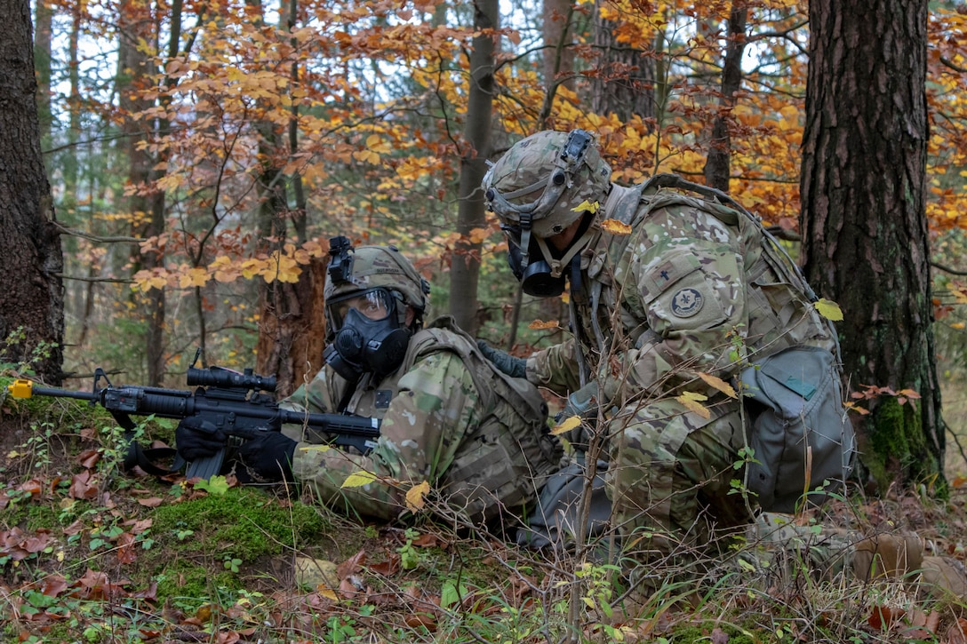 A soldier kneels down next to another soldier on the ground with his weapon pointed.