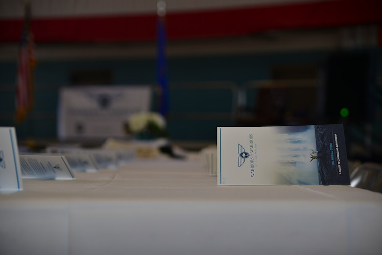 Programs line the tables for the Warriors for Warriors event at Kirtland Air Force Base, N.M., Nov. 2, 2019. Warriors for Warriors is a nonprofit organization that seeks to eradicate cancer, raise awareness and directly help those fighting cancer. (U.S. Air Force photo by Staff Sgt. Kimberly Nagle)