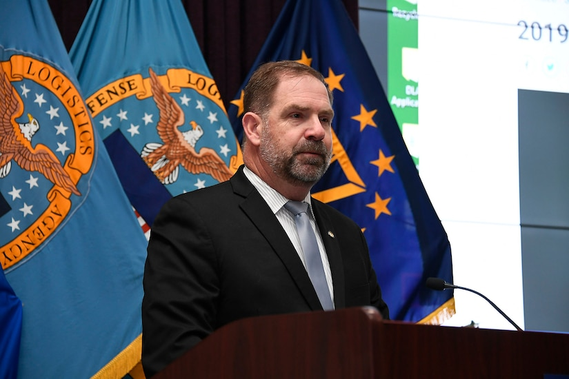 Mike Cannon behind podium with flags in background