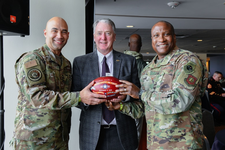 U.S. Air Force Chief Master Sgt. Robert Devall (left), the Aerospace Data Facility-Colorado senior enlisted leader, and Col. Devin Pepper (right), the 460th Space Wing commander, pose for a photo with Joe Ellis, the Denver Broncos president and chief executive officer, Nov. 3, 2019, at Empower Field at Mile High in Denver.
