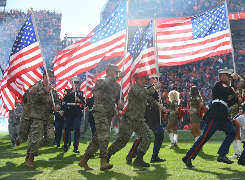 U.S. military service members run onto the field before the Denver Broncos Salute to Service game at Empower Field at Mile High in Denver, Nov. 3, 2019.