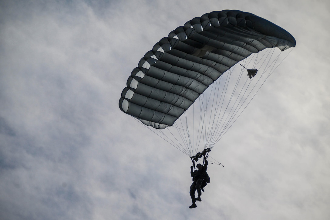 A Marine descends in the sky with his parachute open.