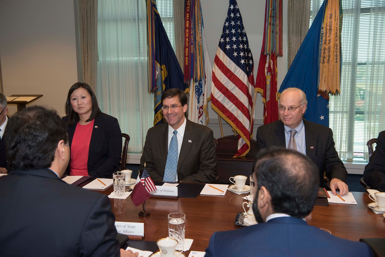 Defense Secretary Dr. Mark T. Esper, center, smiles in a conference room.